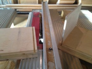 Use a router or table saw to make a rabbet cut along the inside bottom of each of the four panels. The floor piece should slide snugly into the rabbet cut.
